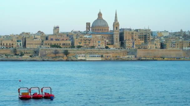 Watch the blue hour medieval Valletta city with its stunning architecture - tower of St Paul's Anglican Pro-Cathedral and dome of Carmelite Church from the Sliema shore, Malta.
