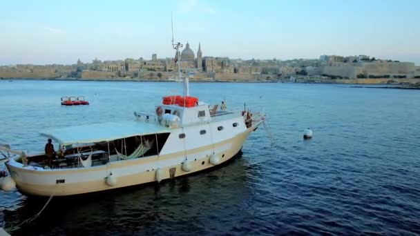 SLIEMA, MALTA - JUNE 19, 2018: The seaside promenade of resort opens the view on moored yachts and iconic skyline of medieval Valletta, seen behind the waters of Northern Harbour, on June 19 in Sliema
