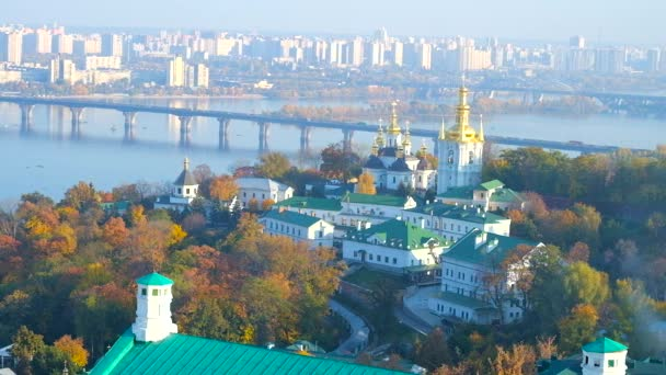 Bell tower of Kiev Pechersk Lavra overlooks Dnieper river with bridges across it and Church of the Nativity of the Blessed Virgin Mary, located on territory of Lower (Far) Caves of Monastery, Ukraine.
