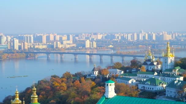 Observe the foggy Dnieper river with its bridges, autumn greenery along the banks and Church of the Nativity of the Blessed Virgin Mary of Lower (Far) Caves of Kiev Pechersk Lavra Monastery, Ukraine.