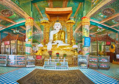 SAGAING, MYANMAR - FEBRUARY 21, 2018: Panorama of the prayer hall of Soon Oo Ponya Shin Paya (Summit Pagoda) with large statue of Buddha Touching Earth, surrounded by rich decors and depictions of Nagar dragons, on February 21 in Sagaing
