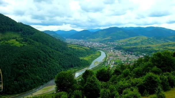 Panorama of Carpathian mountains from the ski lift of Makovytsia Mount, Mizhhiria settlement is seen in valley of Rika river behind the lush mountain forests, Ukraine.