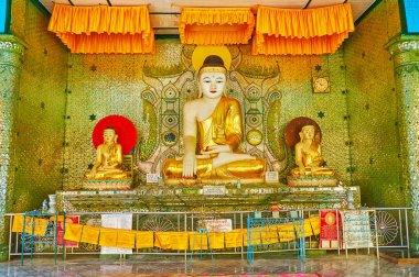 BAGO, MYANMAR - FEBRUARY 15, 2018: The altar of image house of Shwemawdaw Pagoda with statues of Lord Buddha and complex mirror patterns on the wall, on February 15 in Bago.