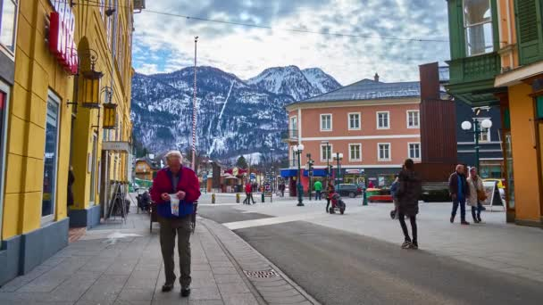 BAD ISCHL, AUSTRIA - FEBRUARY 26, 2019: Walk along crowded Pfarrgasse shopping street with a view on snowy Katrin Mount, old colored edifices, cafes and tall weathervane, on February 26 in Bad Ischl.