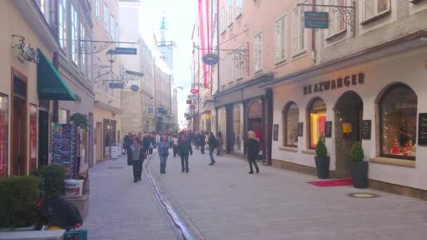 Salzburg, Rakousko - 27 února 2019: Úzké a rušné ulice Getreidegasse nákupní ulice s módními butiky, uměleckých galerií a hodiny věž staré radnice na pozadí, 27. února v Salzburgu