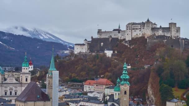 Il castello medievale di Hohensalzburg domina il centro storico di Salisburgo con i suoi palazzi storici, le alte campanili e le Alpi nebbiose sullo sfondo, lAustria