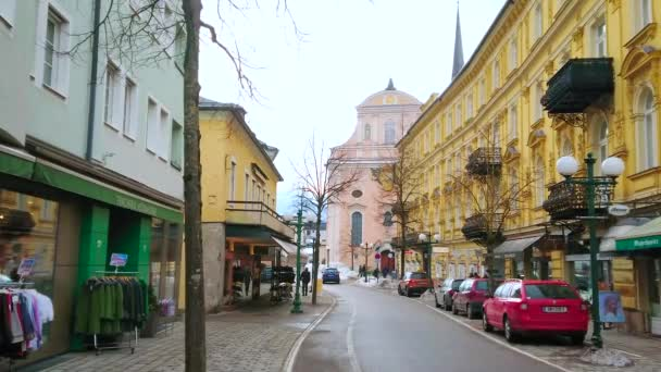 BAD ISCHL, AUSTRIA - FEBRUARY 20, 2019: Franz Joseph Strasse with scenic historic edifices, tourist stores, cafes and St Nicholas Parish Church on background, on February 20 in Bad Ischl