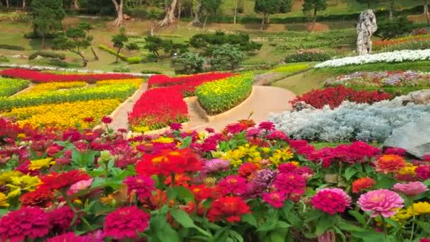 Panorama zahrady Mae Fah Luang s malebnou barevnou květinovými lůžky, které tvoří západní květinové druhy, zdobené keře a tropické stromy, Doi Tung, Chiang Rai, Thajsko