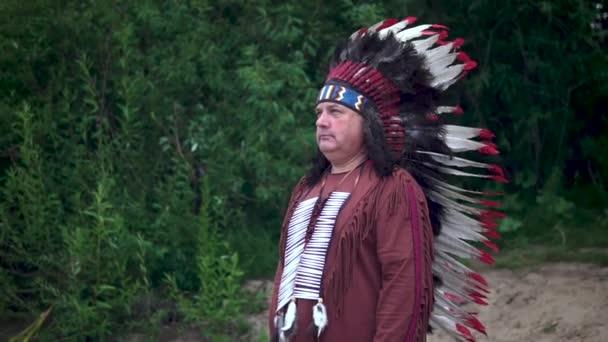 Alte Indianer grüßen und heben die Hand. Steht vor dem Hintergrund des Waldes