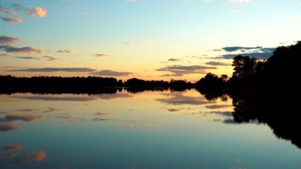 Kilátás a tóra naplementekor. A tó visszatükrözi az eget