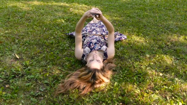 Girl with a phone on the grass