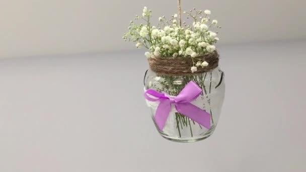 Sklenice s květinami visícími
