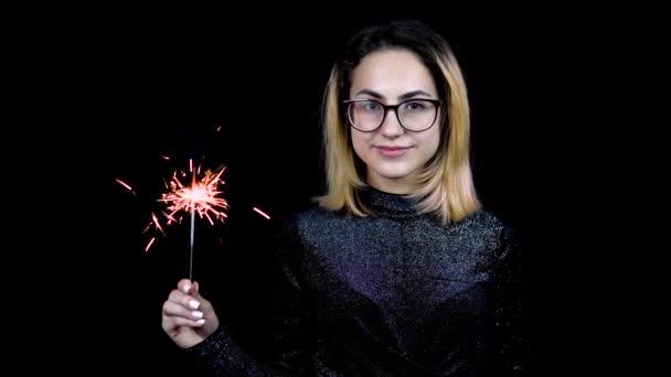 Dívka drží v ruce jiskříka. Mladá žena s brýlemi stojí v lesklých večerních šatech na černém pozadí. 4k