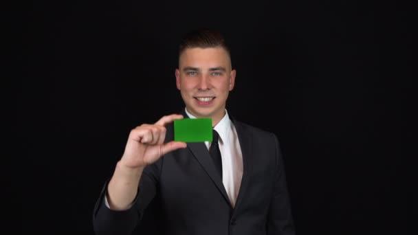 Mladý obchodník v obleku drží v ruce bankovní kartu. Izolované černé pozadí. Zelená karta Chromakey. 4k
