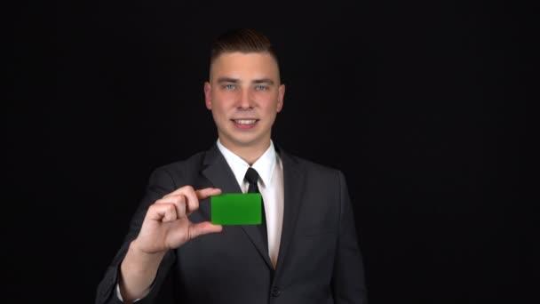 Egy öltönyös üzletember bankkártyát tart a kezében. Elszigetelt fekete háttér. Chromakey zöld kártya. 4k