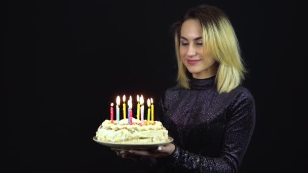 A lánynál van egy karácsonyi torta gyertyákkal. Egy fiatal nő áll fényes estélyi ruhában. Elszigetelt fekete háttér