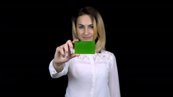 Mladá obchodnice v bílé košili drží v ruce bankovní kartu. Izolované černé pozadí. Zelená karta Chromakey. 4k