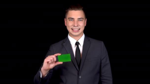 Fiatal üzletember bemutatja a bank zöld kártyát, és azt mutatja, mint a kezét. Chromakey zöld kártya.