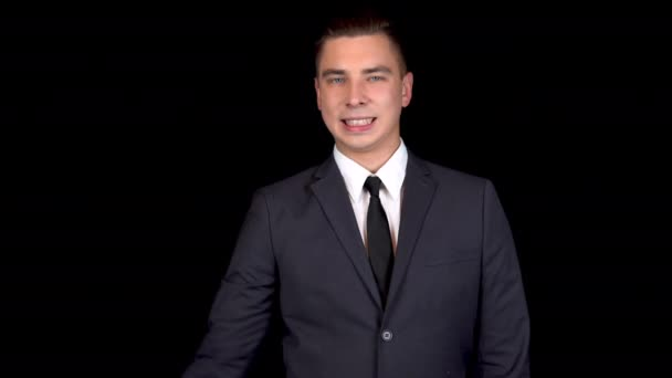 Young businessman shows biceps on his arm. Man in a black suit on a black background