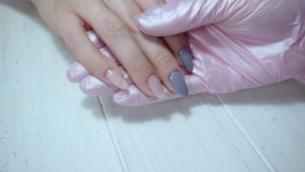 Manikérka kontroluje nehty kvůli oslnění.