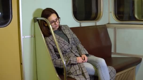 A young woman fell asleep on a subway train. Old subway car
