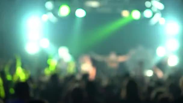Žena na hudebním koncertě zvedla ruce. Smějící se dav před pestrobarevnými světly jeviště. Siluety koncertního davu v předních světlech jeviště.