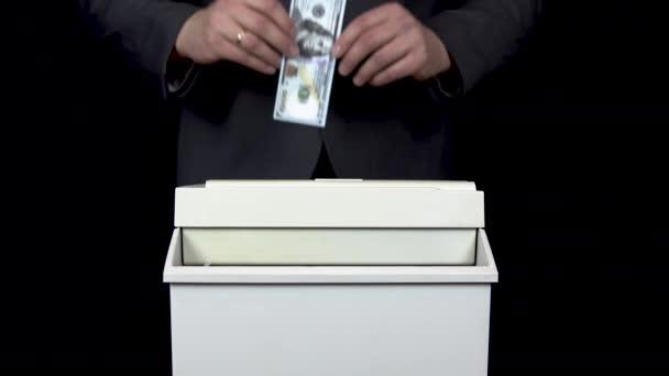 Schroeder destroys one hundred dollar bill. Businessman in a suit thrusts money into a paper shredder