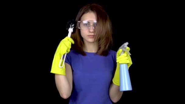 Eine junge Frau kämmt ihre Haare mit einer Klobürste. Frau in Schutzbrille und Handschuhen mit Werkzeug für die Toilettenreinigung. Mädchen hält Klobürste und Spray. auf schwarzem Hintergrund