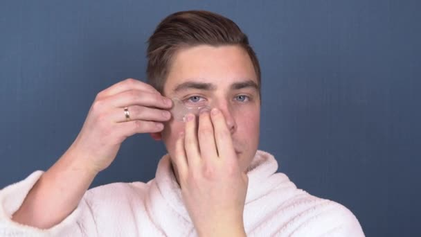 A young man puts patches on his face. Blue hydrogel patches for rejuvenating the skin of the face. Man sitting in a white coat. Close up