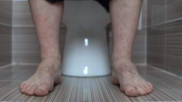 The man took off his black panties while sitting on the toilet. A man with hairy legs in the toilet