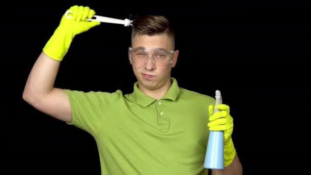 Ein junger Mann kratzt sich mit einer Klobürste am Kopf und kommt auf eine Idee. Mann mit Schutzbrille und Handschuhen für die Toilettenreinigung. Der Typ hält eine Klobürste und ein Spray in der Hand. auf schwarzem Hintergrund