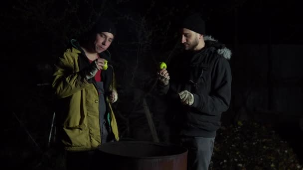 Two homeless young men are frying apples on a fire. Men stand at night near a barrel of fire and bask.