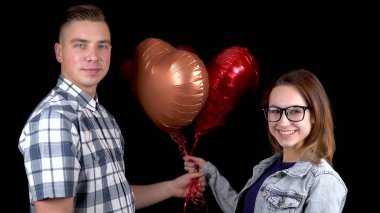 A young man gives a young woman heart-shaped balloons. Man and woman kissed on a black background. Valentines Day is the day of all lovers.