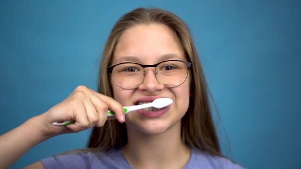 Mädchen mit Zahnspange putzen ihre Zähne mit einer Zahnbürste Nahaufnahme. Ein Mädchen mit farbigen Zahnspangen hält ihre Zähne sauber.