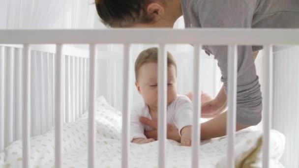 Junge Mutter kümmert sich um Baby im Schlafzimmer