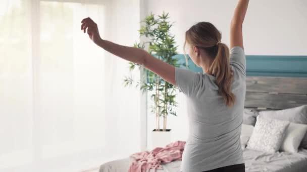 fröhliche schwangere Frau im Schlafzimmer