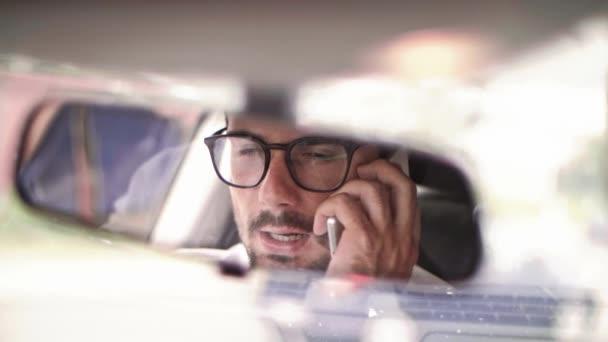 Mann telefoniert mit Smartphone im Auto