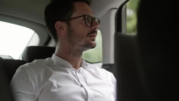 Podnikatel s použitím telefonu v taxíku