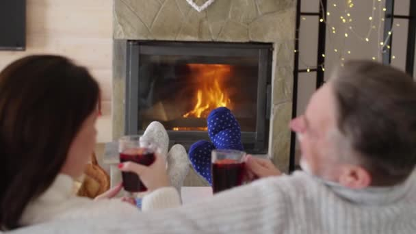 Mature couple with tea relaxing by the fireplace