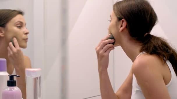 Žena použití kosmetických produktů na její tvář v koupelně