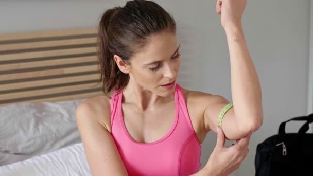 Portrét štíhlé ženy měření její biceps