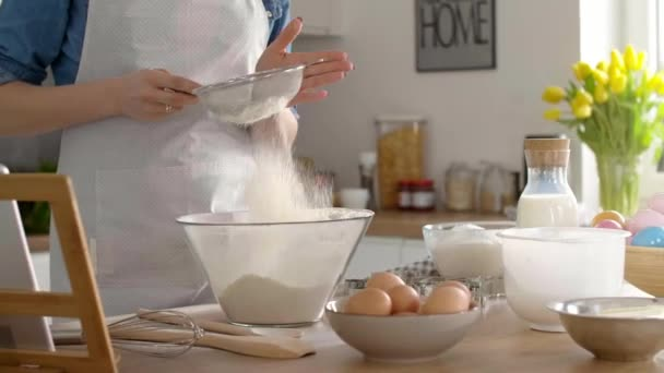 Woman sifting flour in the kitchen