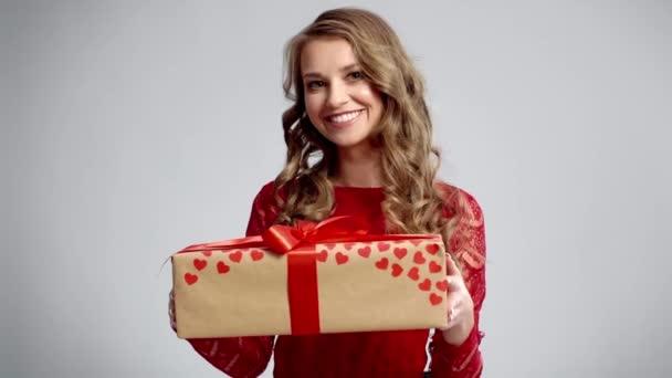 Usmívající se žena držící velký dárek