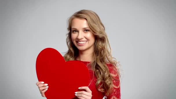 Happy woman holding valentine card with copy space