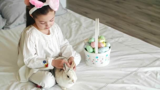 Child and rabbit spending easter morning in bed