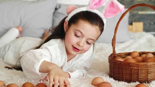 Boldog lány játszik a húsvéti tojás az ágyban