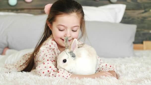 glückliches Mädchen spielt mit Kaninchen auf dem Bett