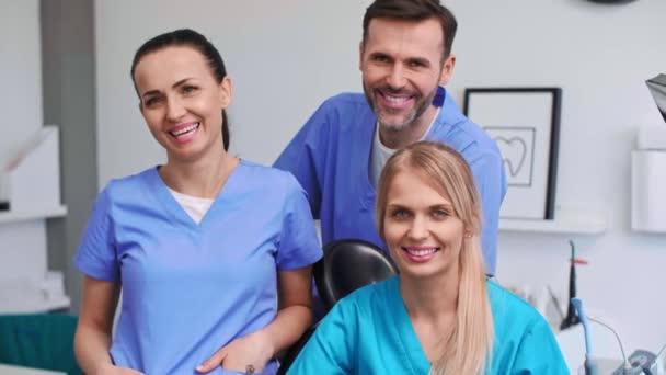 Porträt dreier lächelnder Zahnärzte in der Zahnarztpraxis