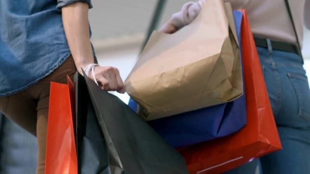 Low section of women with shopping bags in shopping mall