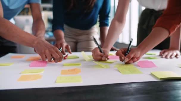 Üzletemberek ötleteket ragasztanak a ragasztó